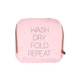 Light Pink laundry bag with gold font that reads Wash Dry Fold Repeat. Bag appears folded into a square.